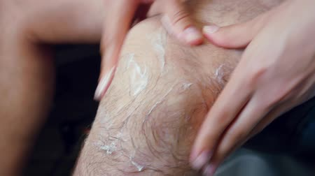 lower part : Close-up of female hands making a massage on mans knee Stock Footage
