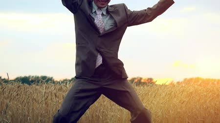 podnikatel : Happy businessman dancing in a field during sunset in slowmotion. 1920x1080