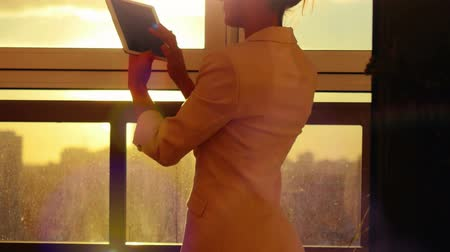 programování : woman using tablet with sunbeams and lens flare Business girl young adult against sunset sky window on blurred city background. 4k Dostupné videozáznamy