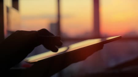 checagem : close up woman hand using tablet in town on sunset and blurred city background. 1920x1080. hd Vídeos