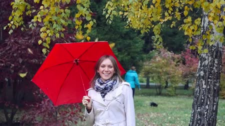 ortam : Beautiful girl with red umbrella at autumn park during fall leaves. 4k