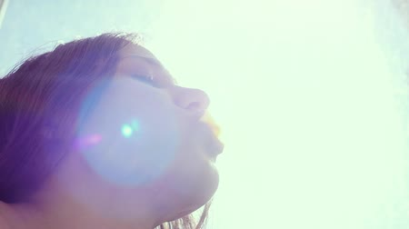 камедь : Girl doing bubble with chewing gum on the sky bacground with the sun and lensflare in slowmotion. 1920x1080