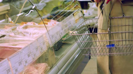 add to cart : NOVOSIBIRSK, RUSSIA, 14 APRIL 2015, Close up of mature woman chooses meat products and add to cart some meat in grocery store. Stock Footage