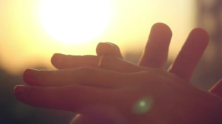 ring : Groom slipping ring on finger of bride on sunset city background in slowmotion. 1920x1080 Stock Footage