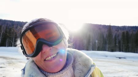esqui : Happy adult woman smiles against mountains in winter in slowmotion on the sun background. 1920x1080