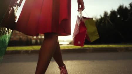stuff bag : Shopaholic woman in beautiful dress holding many shopping bags walking on the street through the sun during sunset in slowmotion. 1920x1080 Stock Footage