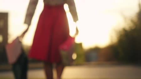 contentamento : Blurred shopaholic in beautiful dress holding many shopping bags walking on the street through the sun during sunset in slowmotion. 1920x1080 Stock Footage