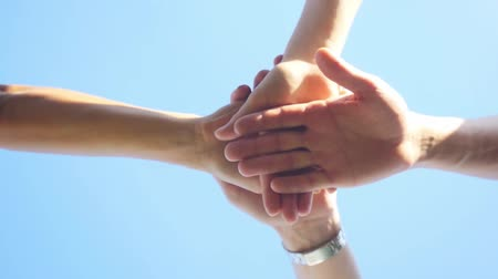 apropriado : Successful team: many hands holding together on sky background in slowmotion. 1920x1080 Vídeos