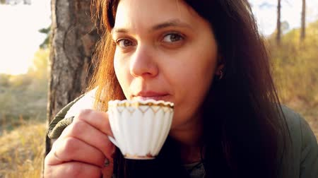 hot beverage : Young beautiful woman having hot tea at sunset relaxing and enjoying nature scene in slowmotion. 1920x1080 Stock Footage