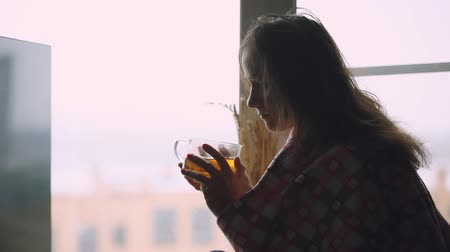 cobertor : Frustrated sad sick woman in plaid sitting on a window sill drinking tea and thoughtful looking in window. 1920x1080