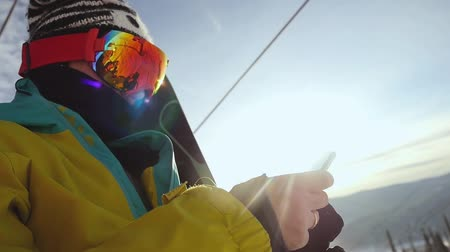 esqui : Skier in glasses with mobile phone on chair lift through the sunshine in slow motion. 1920x1080