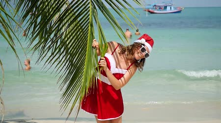 hat : Young joyful woman in santa hat look out from palm tree of branch on tropical beach in slow motion. 1920x1080