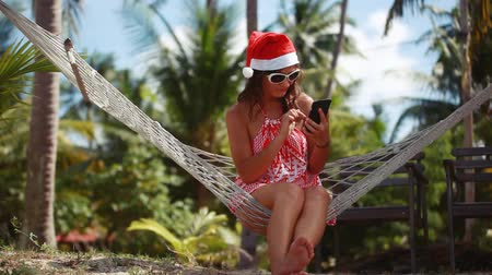 гамак : Young beautiful woman in sunglasses and christmas hat in hammock uses mobile phone on tropical beach celebrating Christmas on Koh Samui. Thailand. 1920x1080