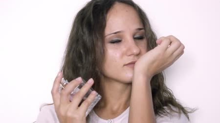 perfume bottle : Young beautiful woman spraying perfume on her wrist on the white background. 3840x2160 Stock Footage