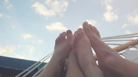 гамак : View on young couple feet rest in hammock on the sky background in slwomotion. 1920x1080. hd Стоковые видеозаписи