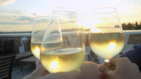 na zdraví : Group of people toasting and drinking wine on the restaurant terrace over sunset in slowmotion with lense flare effects. Celebrating. 1920x1080