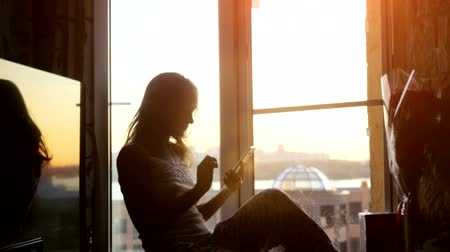 olhares : Beautiful young woman sitting on window uses smart phone on background of the sunset and city. 3840x2160 Vídeos