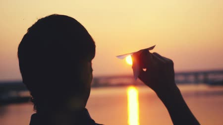 paper airplane : Young guy launch paper plane against the sea during sunset with sun flare and reflections in the water, as in childhood in slowmotion. 1920x1080 Stock Footage