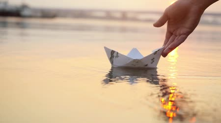 riga : Mans hand launches paper boat on the water and pushing it away during beautiful sunset with reflection sun in the sea in slowmotion. 1920x1080