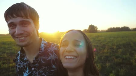 gidip : Happy young couple hugging on summer field and smiling, make selfie having fun outdoors in slowmotion. Countryside. Man and woman on the meadow. Beautiful sun flare. 1920x1080