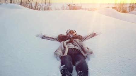 deep snow : Happy young woman falling down in winter lying in snowdrift in slowmotion during sunset time with sun rays. 1920x1080
