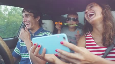 aventura : Happy family with child taking selfie with smartphone play the fool blowing of soap bubbles happy driving in car in slow motion. 1920x1080