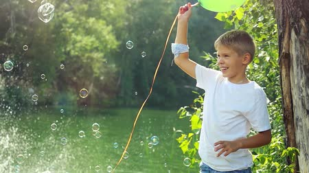 наслаждаться : Handsome happy boy holds green balloon having fun with soap bubbles outdoors on summer in sunny day in slow motion. 1920x1080 Стоковые видеозаписи
