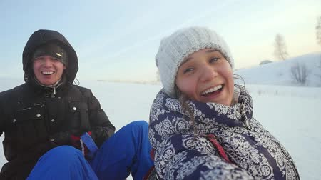 родной брат : Happy young couple are sledding in the mountain through the ssnow in slow motion on sunny day and recording themself on video. 1920x1080