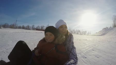 сестра : Happy sister and brother are sledding in the mountain through the sun in slow motion on sunny winter day and recording themself on video with action camera. 1920x1080