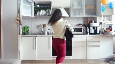 fur headphones : Joyful young beautiful woman is dancing in kitchen with her adorable Maine Coon cat wearing headphones in the morning listening to music on smartphone. 3840x2160