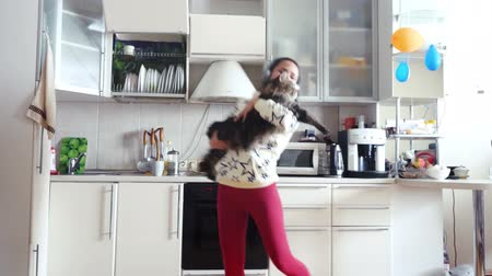 fur headphones : Happy young beautiful woman is dancing in kitchen with her adorable Maine Coon cat wearing headphones in the morning listening to music on smartphone. 3840x2160