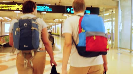 proceed : Passengers with backpacks on travelator in international airport. 3840x2160, 4k