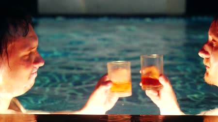wódka : Happy friends raising toast with vodka relaxing in pool. 3840x2160