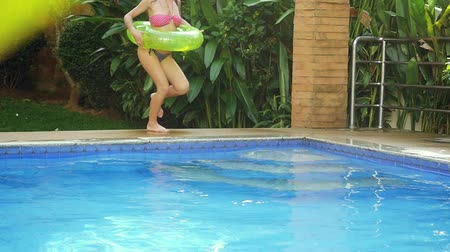 outside : Happy young brunette sexy woman with an inflatable circle runs into the swimming pool in slow motion. 1920x1080 Stock Footage