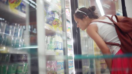 errands : Thailand, Koh Samui, 12 december 2015. Woman shopping in supermarket choosing milk yogurt and puts in trolley. Stock Footage