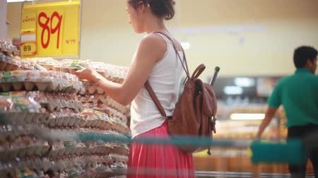 uložit : Young woman with backpack buys eggs at the supermarket puts in a trolley. 1920x1080