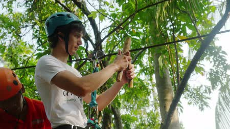 contender : Thailand, Koh Samui, 26 january 2016. Canyoning instructor explains the tourist man how to hold onto a slingshot on a cable descent in tropical jungle. 3840x2160, 4k