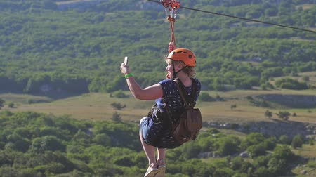 hamlet : Russia, Crimea, 3 july 2017. Young happy woman sliding on high speed zipline rope above beautiful mountain with phone taking video in slow motion. 1920x1080