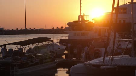 soczi : Russia, Sochi, 12 july 2017. Luxury yachts at amazing golden sunset sea water on promenade with lens flare effects. slow motion. 3840x2160