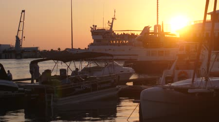 yüksek çözünürlüklü : Russiam Sochi, 12 july 2017. Luxury yachts at amazing golden sunset sea water on promenade with lens flare effects. slow motion. 3840x2160 Stok Video