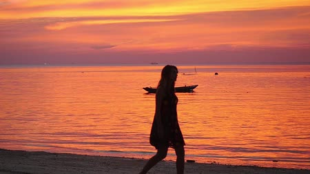 tourist silhouette : Thailand, Koh Phangan, 3 april. 2016. Girl walking on tropical beach at sunset walking barefoot holding shoes in hands. slow motion. 1920x1080