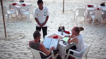propor : Koh Phangan, Thailand, 9 april 2016. Couple sit in beach cafe with menu. Romantic dinner on the beach and waiter stands next to the table. 1920x1080 Vídeos