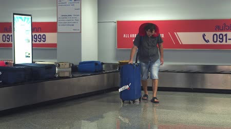 Singapore, 13 july 2018. Airport baggage claim. Young man traveler takes his luggage from conveyor. 3840x2160