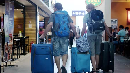 Malaysia, Kuala Lumpur, 13 july 2018. Two traveling man with backpacks walking at airport are pulling suitcases slow motion. 3840x2160 Vídeos