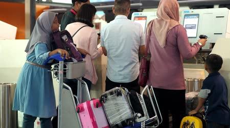 Malaysia, Kuala Lumpur, 13 july 2018. Asian big family check-in luggage on a conveyor in the airport. 3840x2160