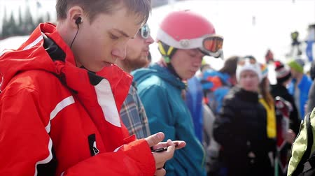Russia, Sheregesh, 18 april 2018. Skier listens to music in headphones uses mobile phone while stands in queue to ski lift. slow motion. 3840x2160