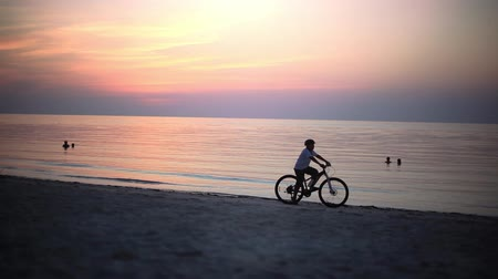 Koh Phangan, Thailand, 11 april 2018. Mans silhouette riding bicycle in helmet on tropical beach during sunset. 1920x1080 Vídeos