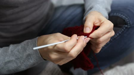 crochet : Closeup womans hands knitting red burgundy wool yarn. Shallow focus. Stock Footage