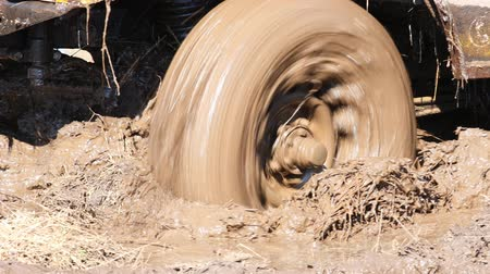 koruyucu : SUV 4WD car stuck in muddy off-road. Closeup of the wheel rotates in the mud. Stok Video