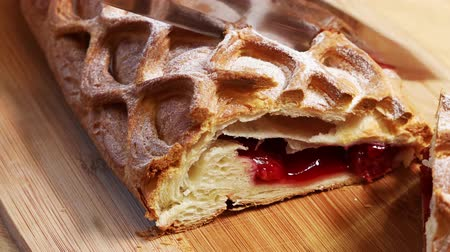 calorias : knife cut off a piece of cherry strudel on wooden plate